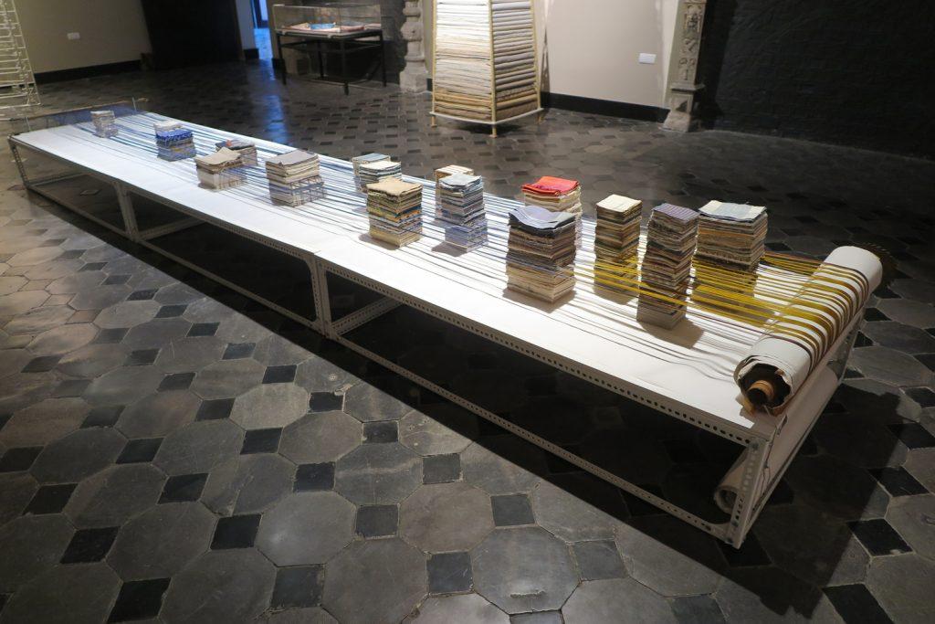 Fine Balance, indigo ikat dyed silk warp, cotton and silk cloth samples, loom beam, paper.                            Curtius museum