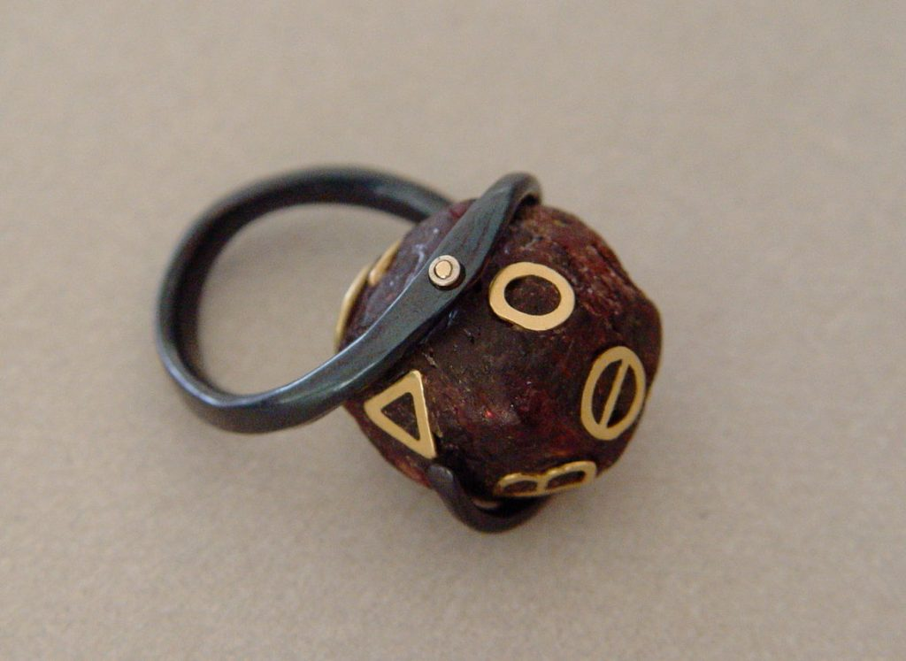 Ring: forged iron, garnet, gold